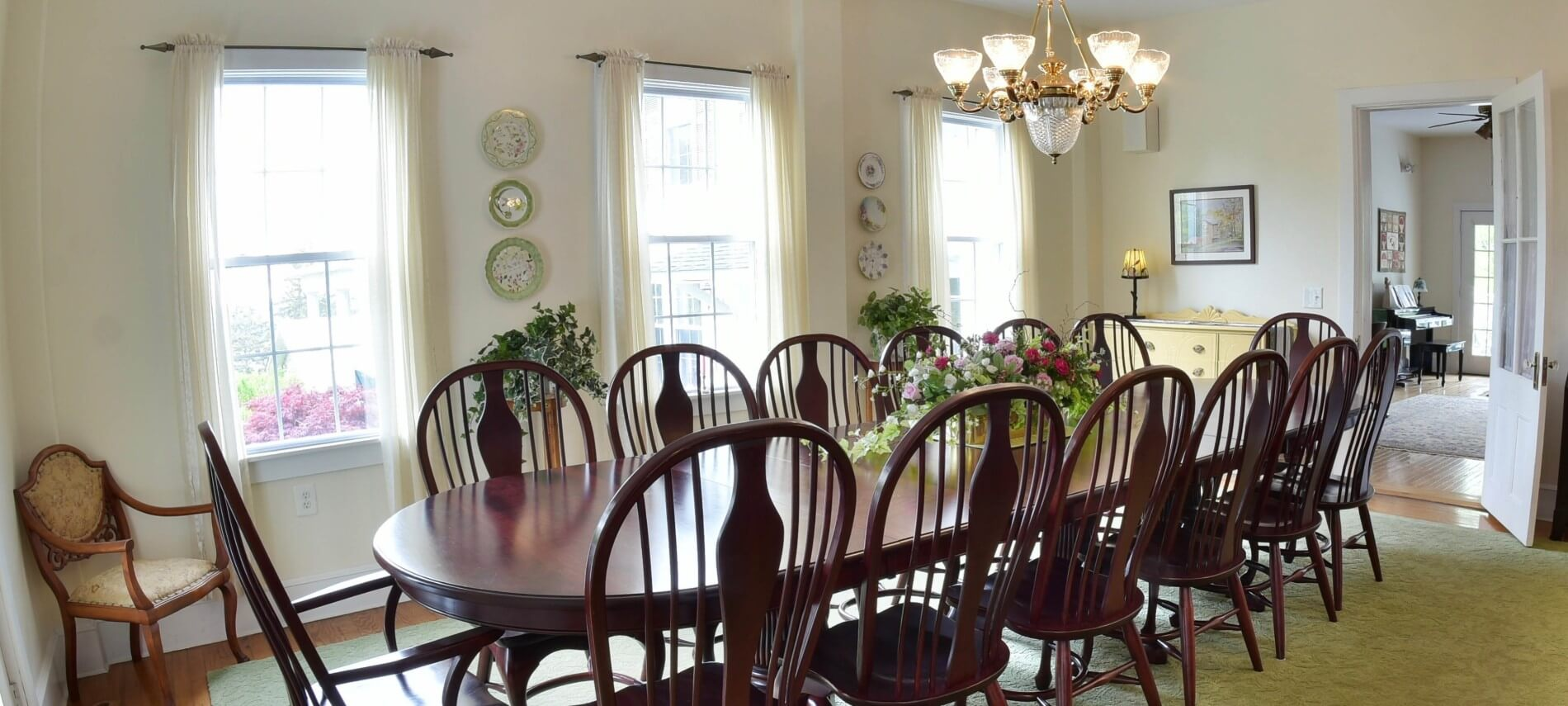 Oval table set for seven in a large dining room decorated in elegant decor.