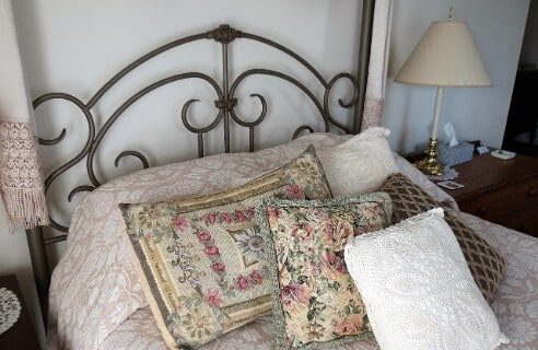 Iron bed is prettily made up with a damask bedspread and needlepoint pillows.