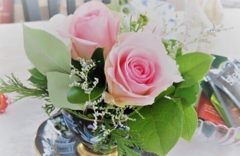 Pink roses with green leaves in a bouquet with baby's breath.