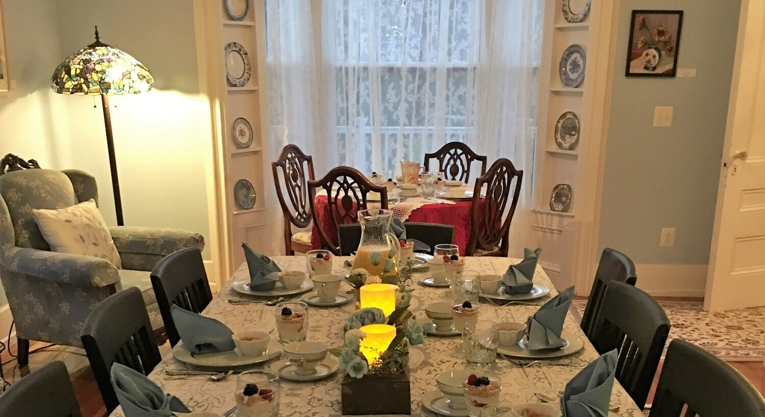 Long dining room table set for breakfast with china and folded napkins.