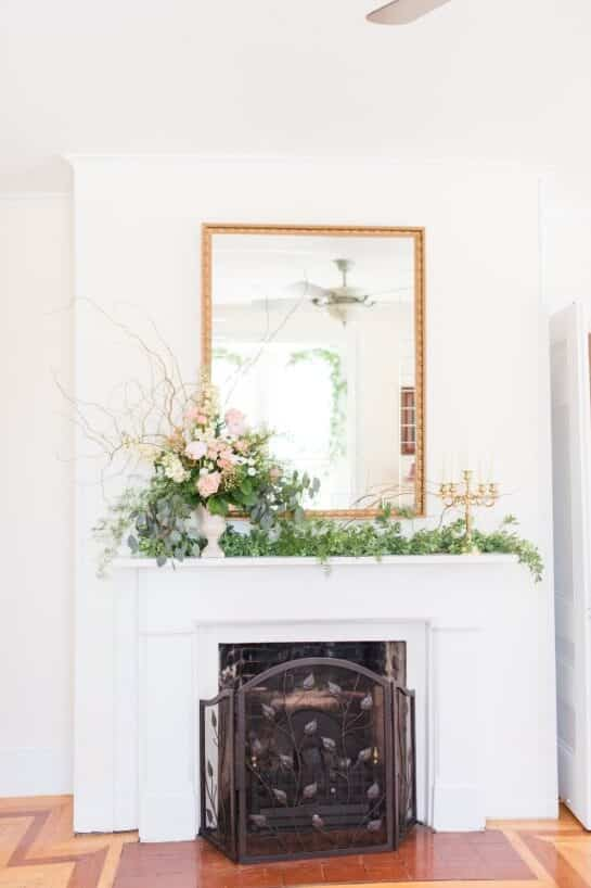 White fireplace with mantel decorated with an effusive pink floral arrangement, fronted by an iron screen.