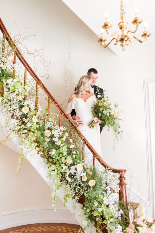 Blonde bride and brunette groom in gown and tux stand on a staircase decorated with pink and white flowers.