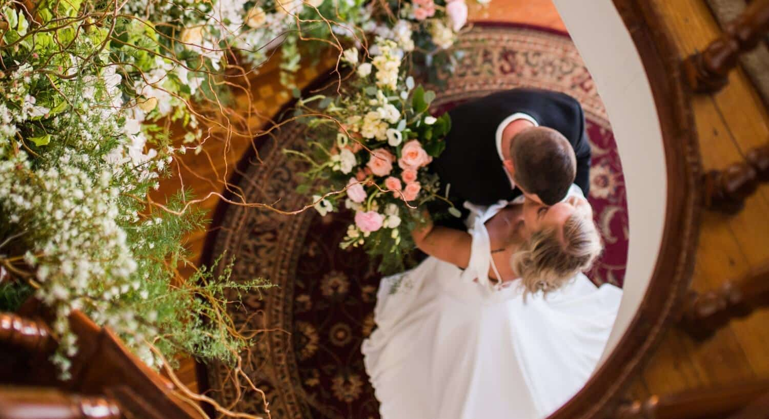 Bride and groom embracing at the bottom of a lavish brown spiral staircase covered in flowers