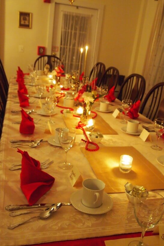 Long dining table set in white with red accents and candlelight.