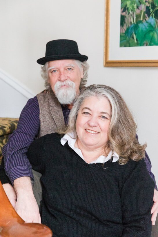 Couple smile at camera while sitting on staircase - man in a hat and woman in a black sweater.