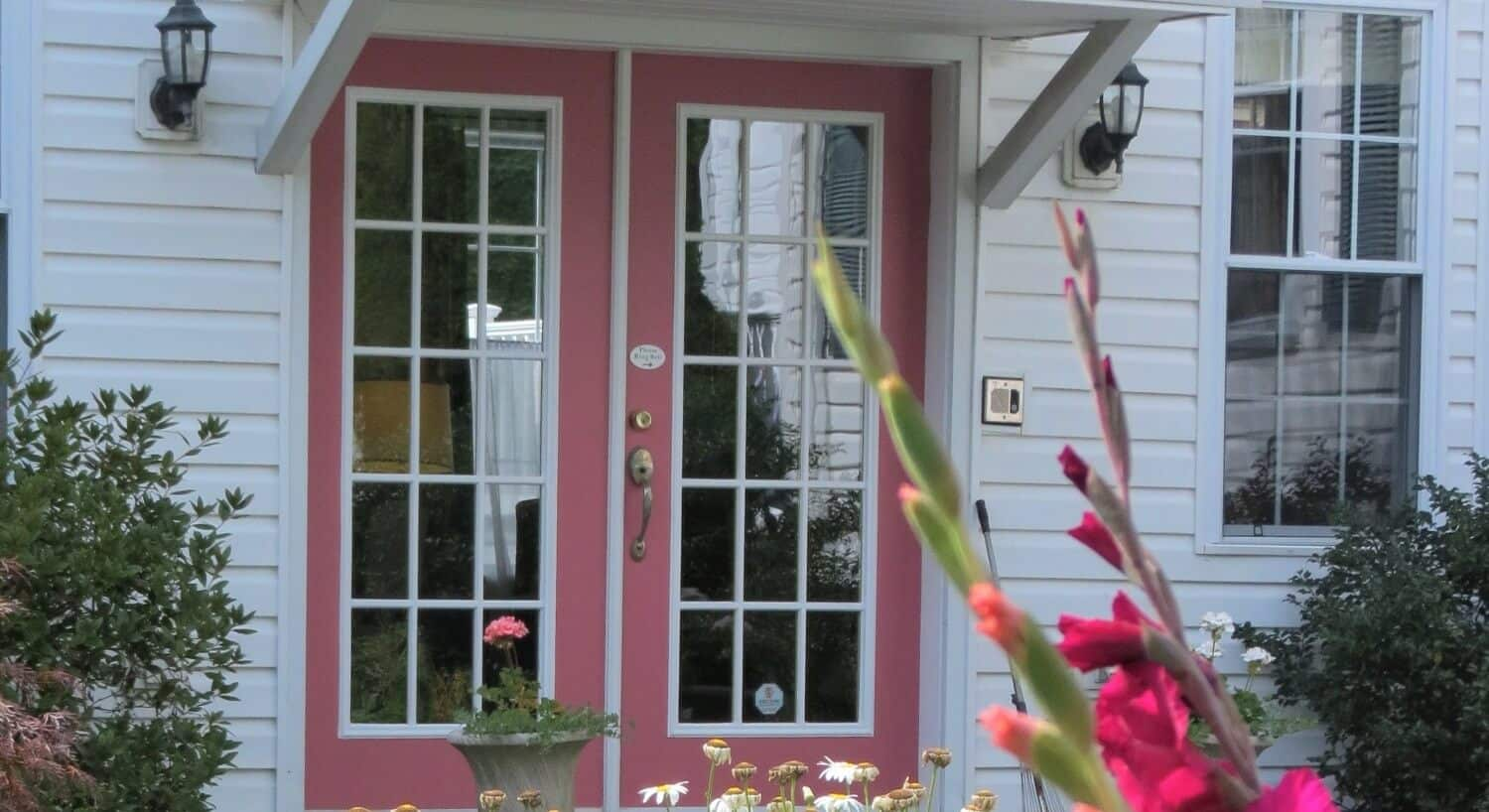 Large pink and white French doors with green bushes outside and pink flowers in foreground