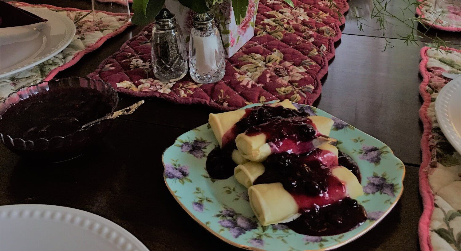 Cheese blintzes covered with blueberry compote on a china plate.