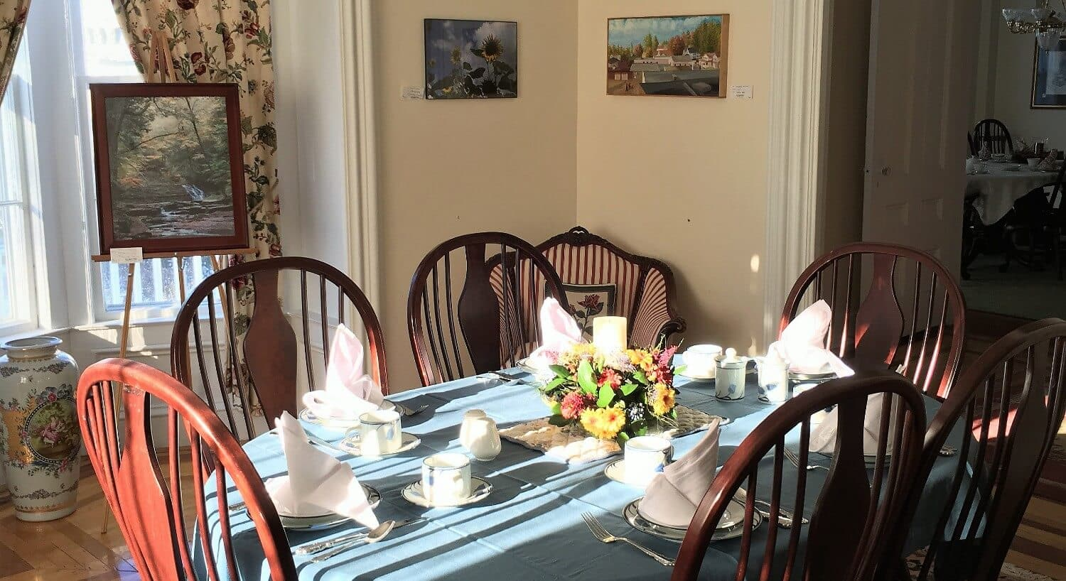 Oval table set for six with tablecloth and napkins in breakfast room.