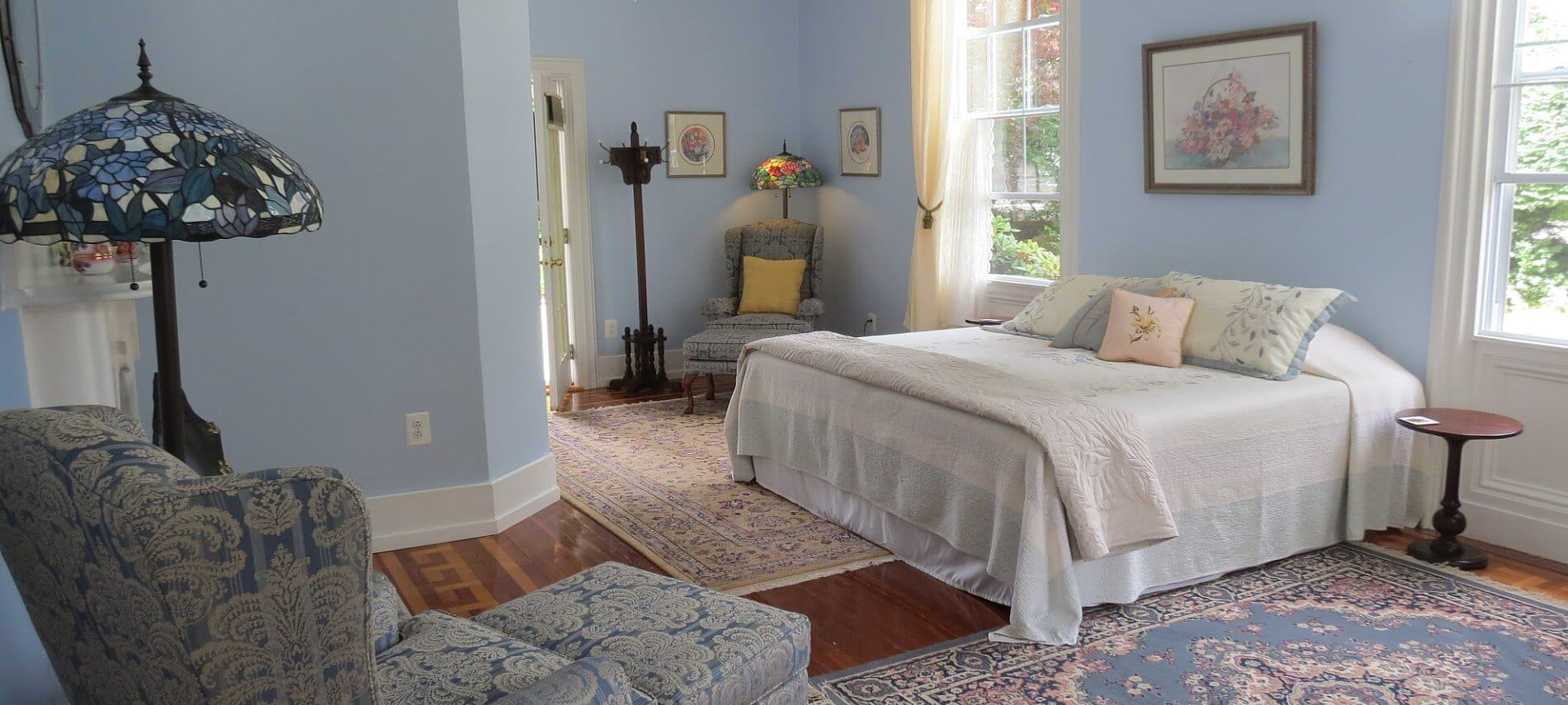 Bedroom decorated in calming blue and white with a queen bed, large windows and chair with ottoman.