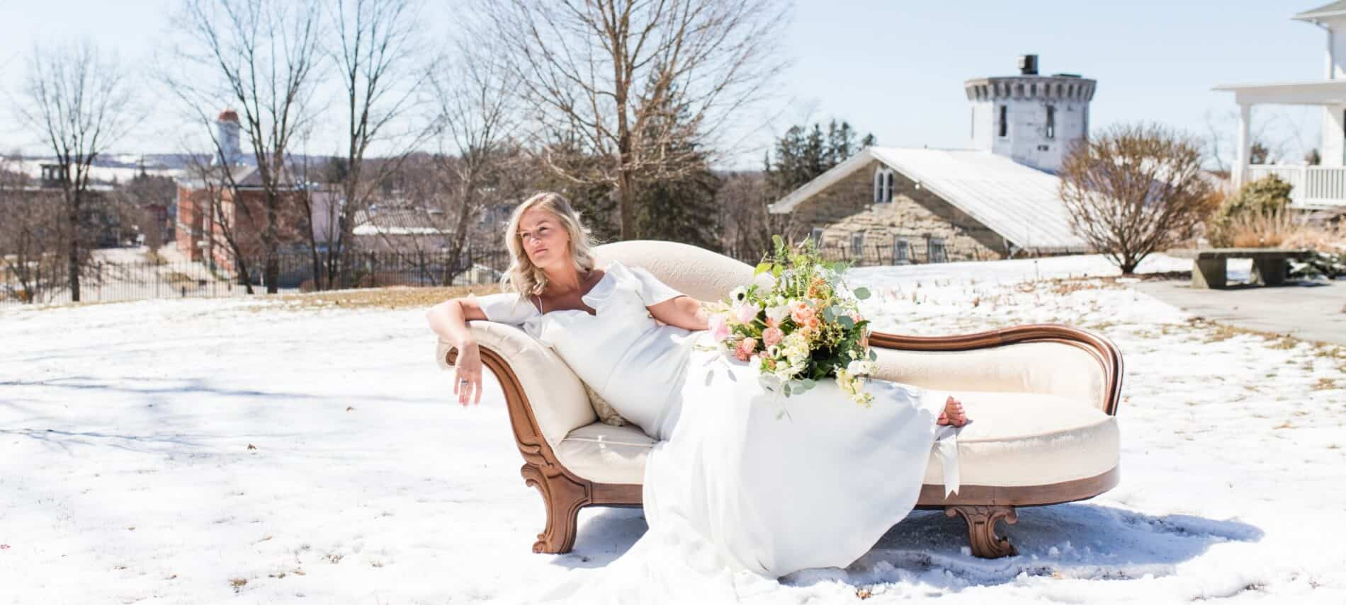 Blonde bride in white gown reclines on a cream settee in a snowy outdoor scene.