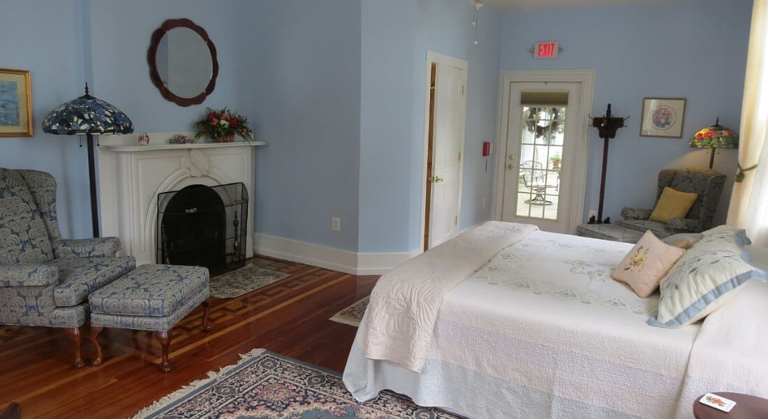 Bedroom decorated in calming blue and white with a queen bed, fireplace and chair with ottoman.