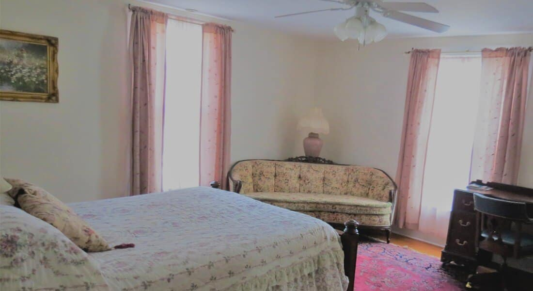 Pretty bedroom decorated in pink and white with a queen bed and antique setee, with a desk.