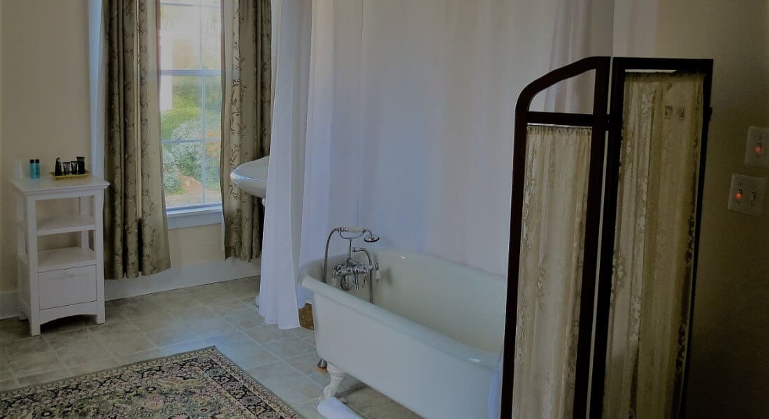 Clean and bright bathroom with a claw-foot tub and large window.