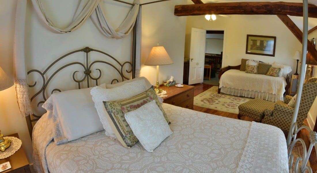 Elegant and large bedroom wwith a canopy bed and daybed made up in white with wooden ceiling beams.
