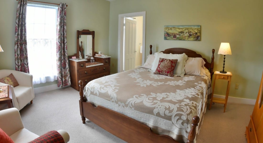 Elegant bedroom furnished with cream armchairs and wooden bed and dressers.