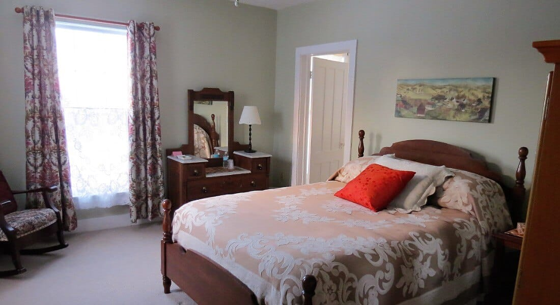 Bright bedroom furnished with a queen bed, rocking chair and a wooden vanity and armoire.