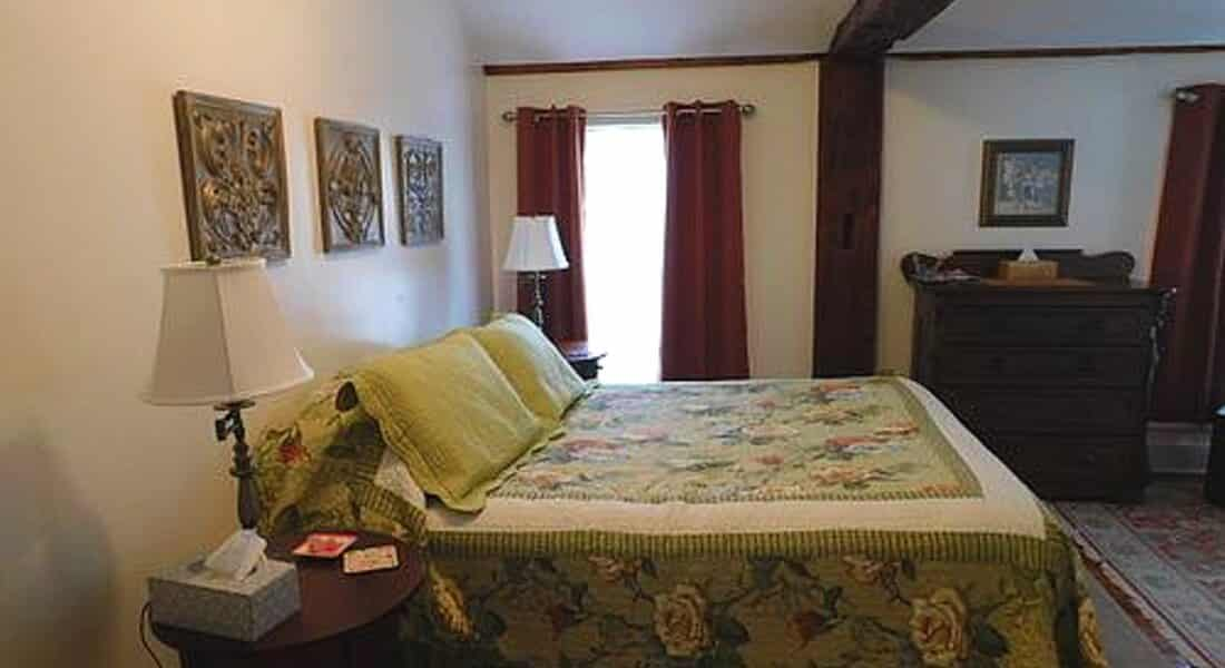 Large bedroom with burgundy drapes, bed made up in a flowerd quilt and a wooden dresser.