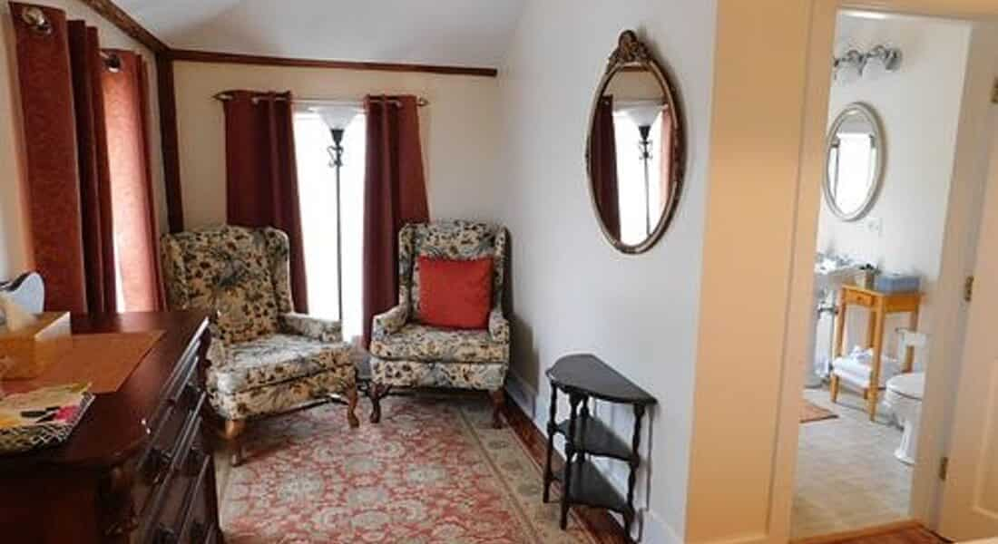 Sitting area in bedroom with two patterned wingback chairs, windows with burgundy drapes and a persian carpet.