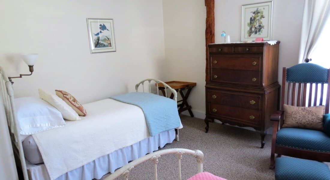 Twin white iron beds in bedroom with rocking chair and wooden dresser.
