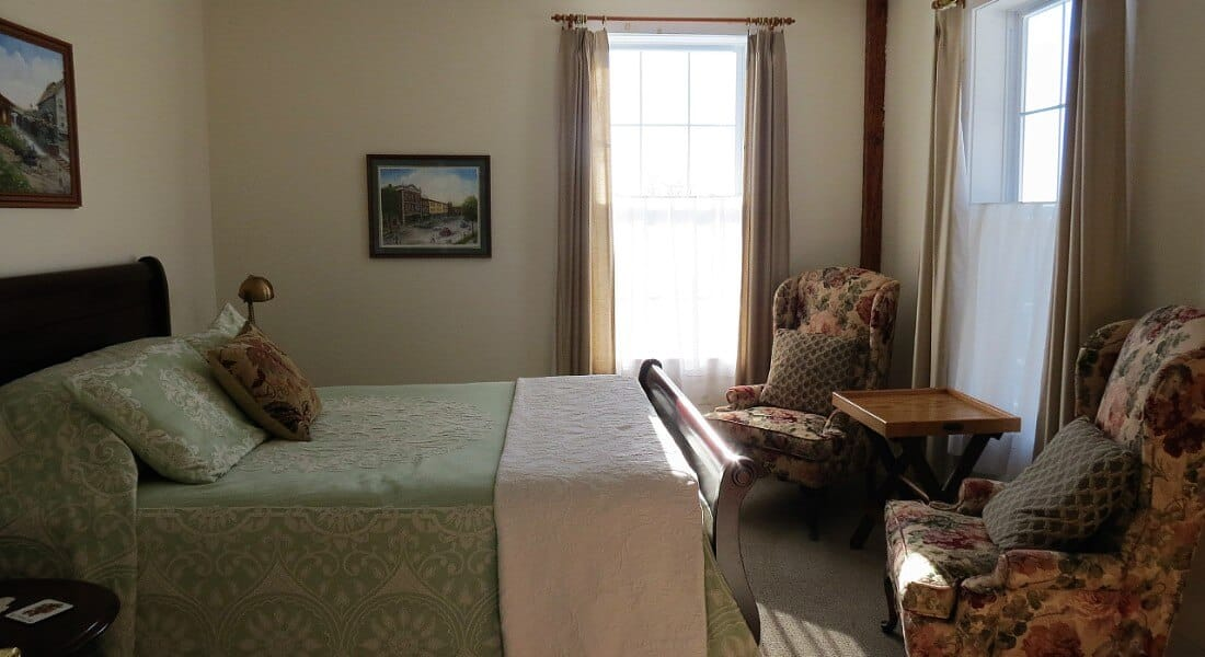 Two wingback chairs face a queen sleigh bed in a bedroom with large windows.