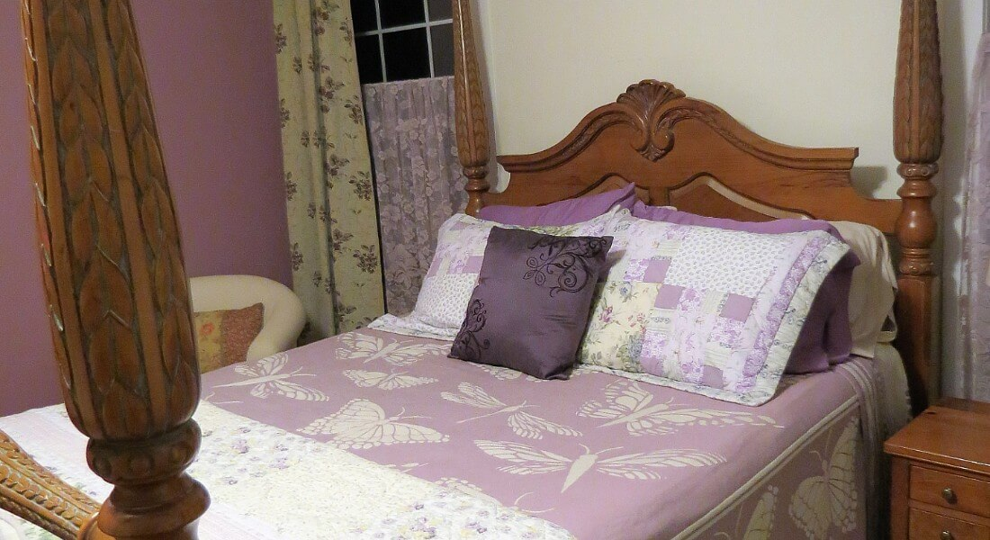 Large four-post bed made up in a lavender butterfly print bedspread and decorative pillows.