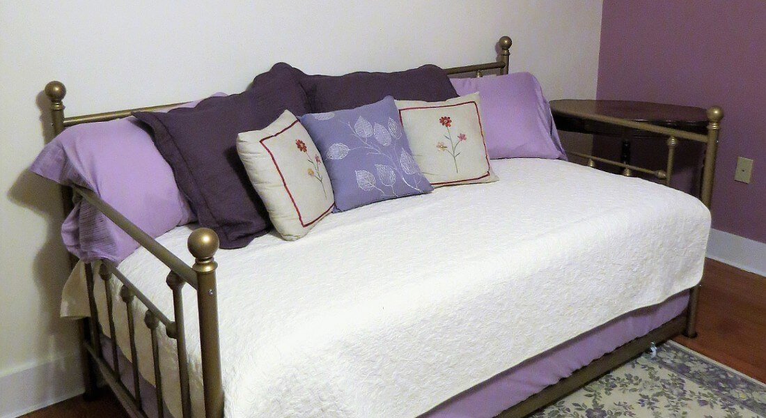 Brass daybed made up in white with lavender sheets and many pillows.
