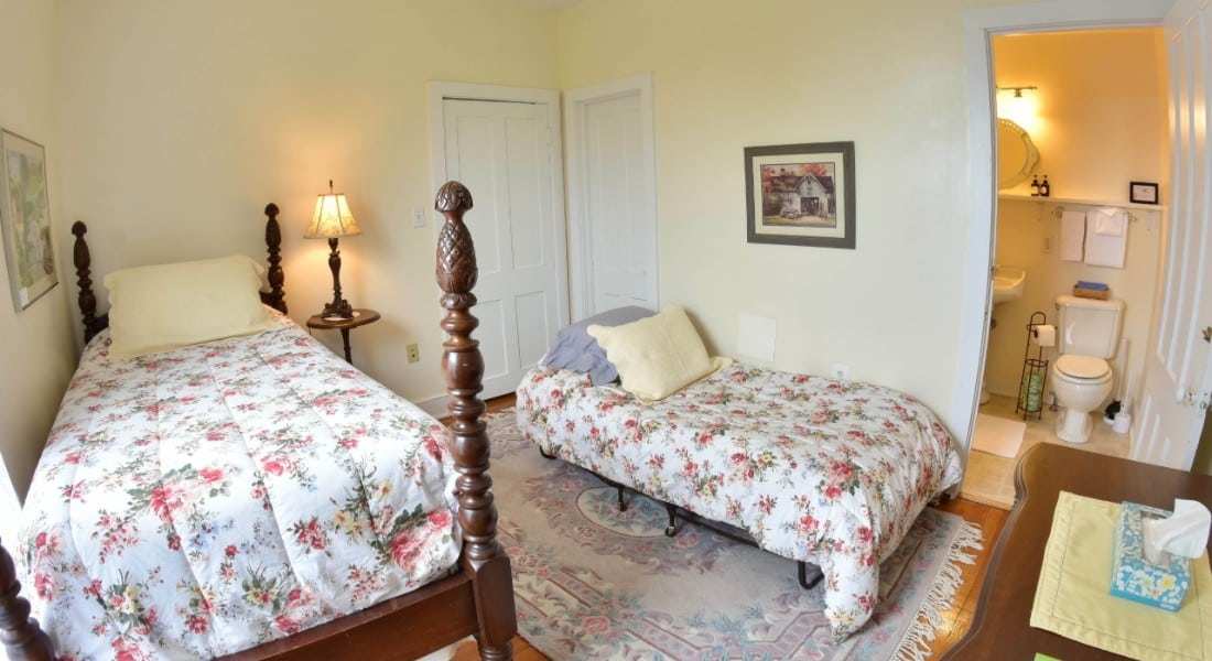 Bedroom with a twin bed and rollaway made up in flowered comforters with an attached bath.