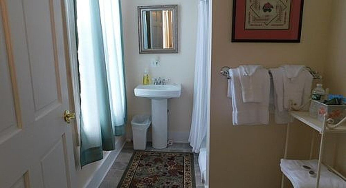 View of bathroom with a pedestal sink, large window and shower.