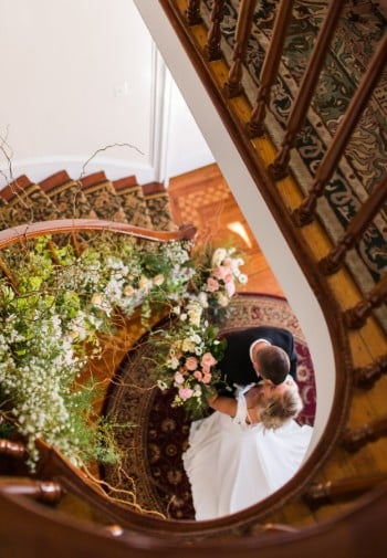 Spiral staircase with wooden spindles and carpet runner, decorated with flowers - bride and groom embracing at bottom.