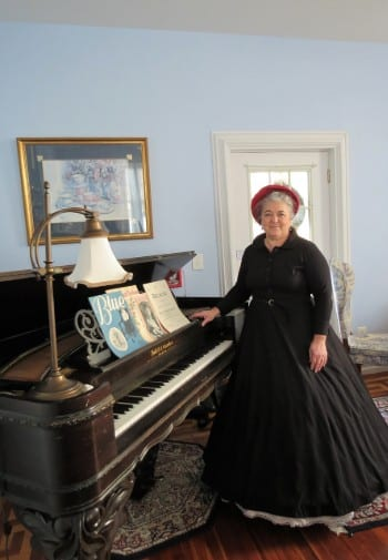 Woman in a black historic gown and hat stands next to a grand piano in a blur painted room.