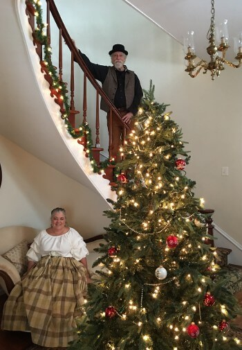 Man and woman inhistorical dress stand near decorated Christmas tree against a spiral staircase.