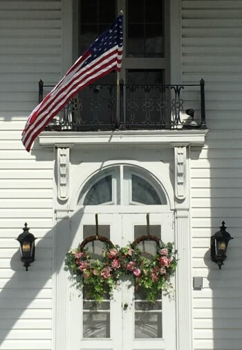 Ornate front doors of mansion, with sidelights and floral wreaths in pink.